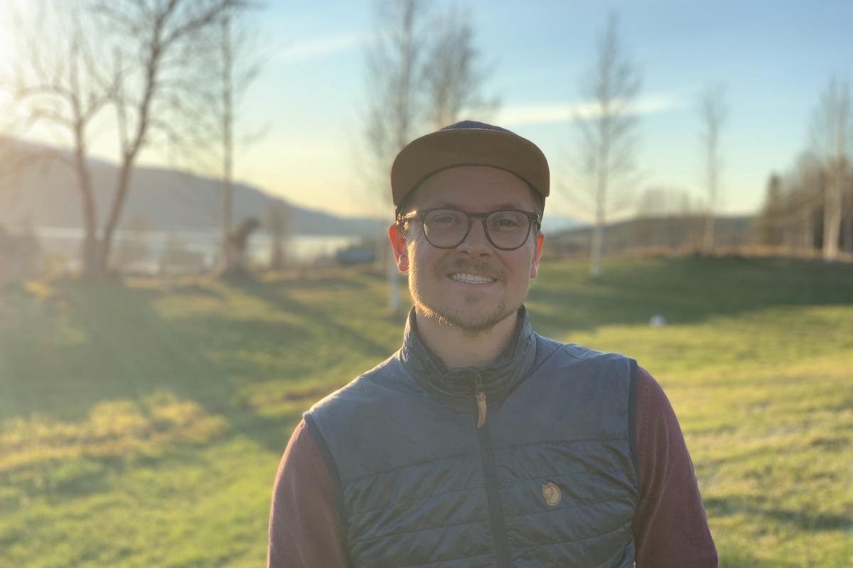 Bilden visar Marcus Ståhl som driver Fjällbyrån, i bakgrunden ser man fjäll och en vacker sjö.